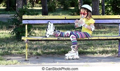 little girl with roller skates drink water