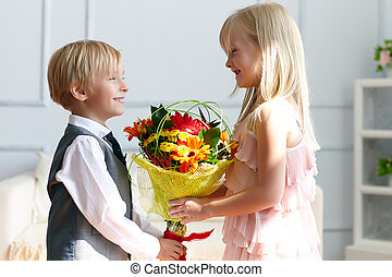 Boy is presented flowers to girl Studio shot