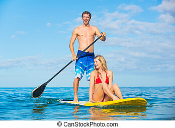 Couple Stand Up Paddle Surfing In Hawaii, Beautiful Tropical...