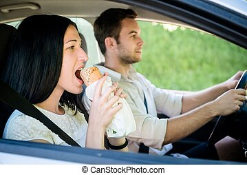 Eating in car - Couple in car - man is driving and woman is...