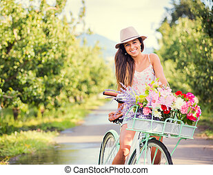 Beautiful young woman on bike in park