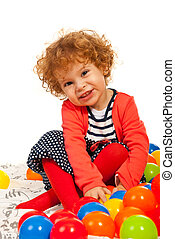 Happy toddler girl with colorful balls