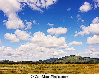 Landscape with mountain views, arable land, blue sky and...