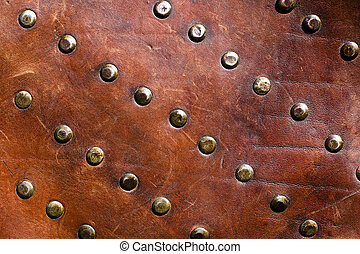 leather with rivets - old brown leather covered with rivets...