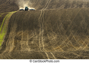 plowed soil - plowed land on a farm in the background with...