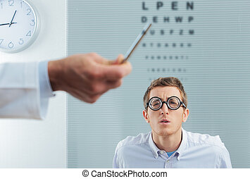 Optometrist Visit - Optometrist pointing at eye chart, a...