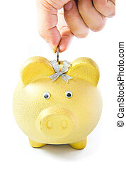 Saving money, male hand putting a coin into piggy bank.