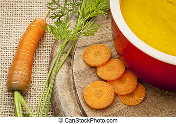 carrot cream soup in a stoneware bowl on canvas background...