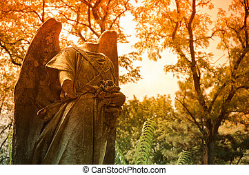 Graveyard scene: headless statue among autumn trees -...
