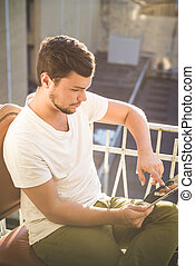 yuong stylish hipster man using tablet on the house balcony