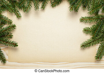 fir twigs on wooden table with paper sheet