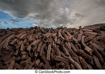 Pile of bog peat drying in a field in Ireland