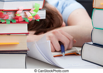 Overworked student sleeping on desk around the piles of...