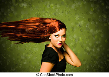girl with wind blown red hair and a green background