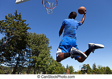 Man Dunking a Basketball - A young basketball player driving...