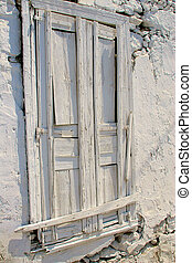 Wooden door painted white in stony wall covered with falling off plaster