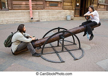 City teeter-totter - Young smiling couple sit on...