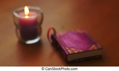 Romantic Book and Candle Rack Focus - Rack focus shot of a...