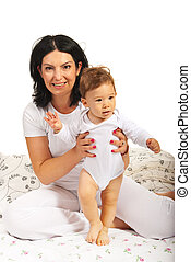 Mother holding baby in bed