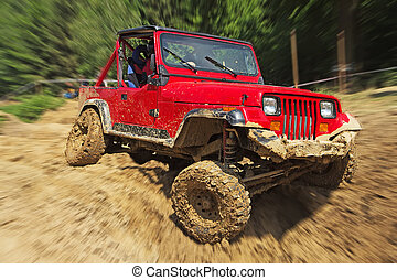 Red off-road car in difficult terrain Blurred background All...