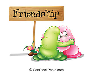 A green and a pink monster hugging near the wooden signage