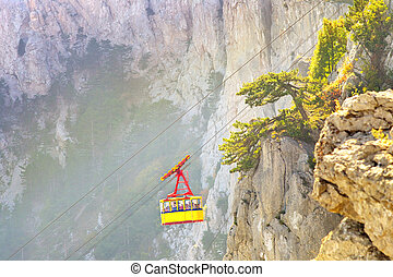 Yellow Funicular Cable with cabin high with Rocky Mountains...
