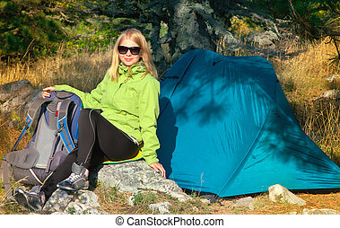Young Woman with Smiling Face Hiker sitting with backpack and Tent Camping Outdoor on Grass with forest nature on background Travel and Healthy Lifestyle concept