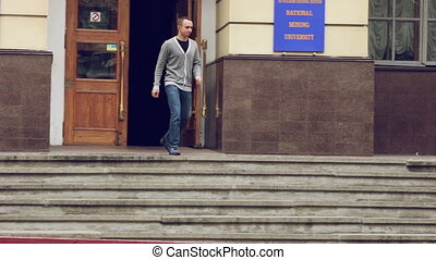 Exit the building - Student coming out of the university and...