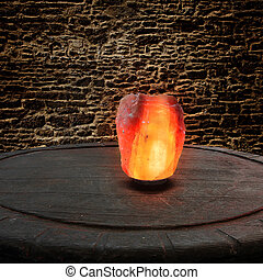 Himalayan salt as a lamp on an old wooden table in front of...
