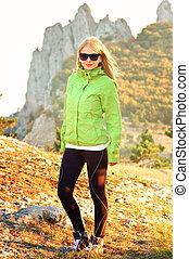 Young Woman Hiker standing Outdoor on Grass and Mountains rocks on background Travel and Healthy Lifestyle concept