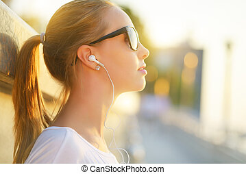 Teenage girl listening to music background of the street