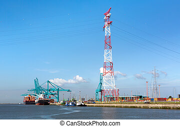 Antwerp harbor - Huge container ships being loaded with...