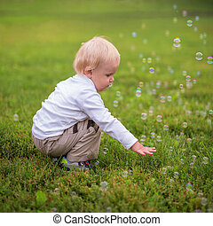 Little boy and soap bubbles, outdoors