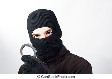 Burglar with handcuffs - Burgler posing with handcuffs and...