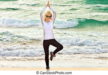 Young Woman Training Sport on Beach Seaside sand with blue Sea on background Fitness and Healthy Lifestyle concept