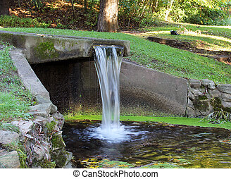 aqueduct - water flows down an aqueduct and falls into a...