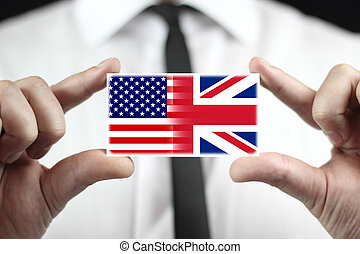 USA and UK Flag - Businessman holding a business card with...