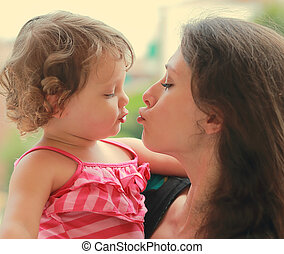 Beautiful young mother and baby girl going to kiss on nature background. CLoseup portrait