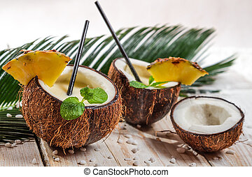 Pinacolada with mint leaf in the coconut