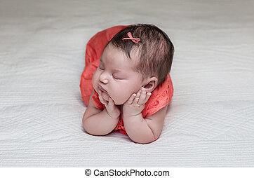Beautiful newborn baby sleeping on her elbows and hands -...