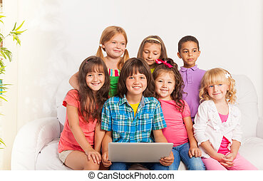 Smiling group of kids with laptop