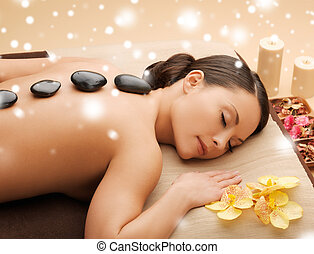 beautiful woman with hot stones - health and beauty concept...