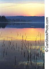 Sunrise on a wild forest lake in  Karelia. Russia