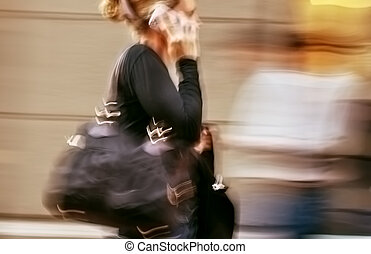 Woman talking on a cell phone in a hurry - Hot day in the...