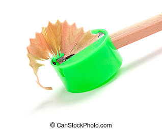 Sharpening a pencil with a green sharpener isolated on white...