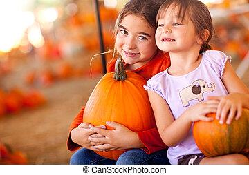 Cute Little Girls Holding Their Pumpkins At A Pumpkin Patch...