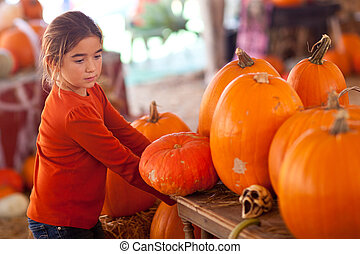 Cute Girl Choosing A Pumpkin at A Pumpkin Patch One Fall Day...