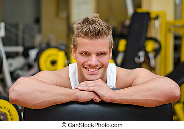Attractive young man in gym resting on gym equipment