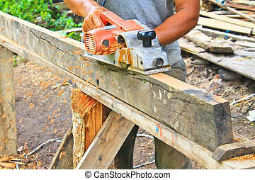 Hand carpenter using wood planer