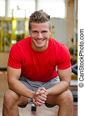 Attractive young man in gym sitting on bench, smiling -...